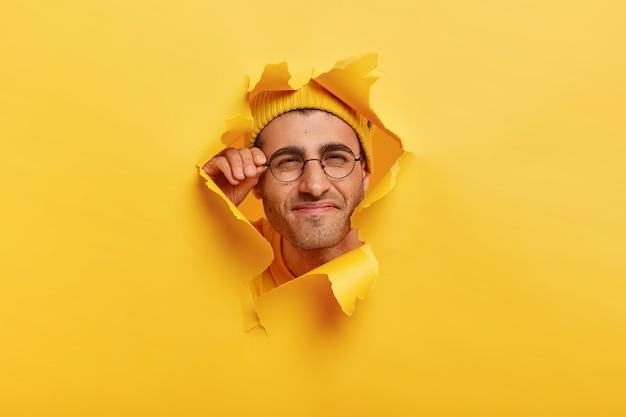 Homem olha através do papel rasgado com curiosidade