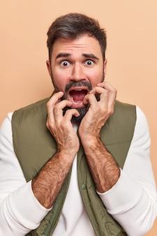 Homem olha em pânico para a câmera engasga com expressão de medo medo de consequências ruins treme de medo assiste filme de terror vestido casualmente