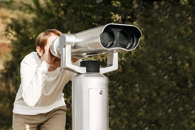 Homem olha em um grande telescópio observação da natureza através de um telescópio