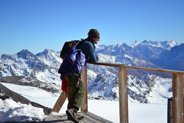 Homem olha para longe na paisagem de montanhas nevadas, uma paisagem de inverno nas montanhas