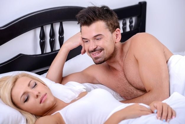 Homem olha para sua esposa enquanto ela está dormindo em seu quarto.