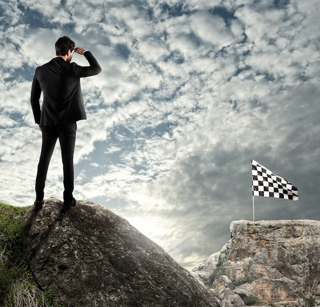 Homem olha para uma bandeira do outro lado da montanha. o conceito de negócio do empresário supera os problemas