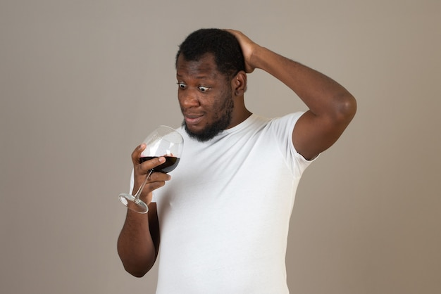Homem olha para uma taça de vinho em sua mão, em frente à parede cinza