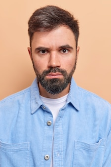 Homem olha sério tem expressão estrita olha diretamente para a câmera usa camisa de veludo azul com sorriso afetado rosto isolado em bege