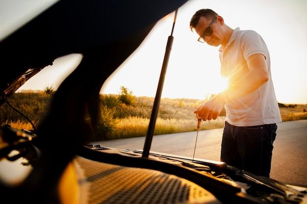 Homem olhando as condições do carro