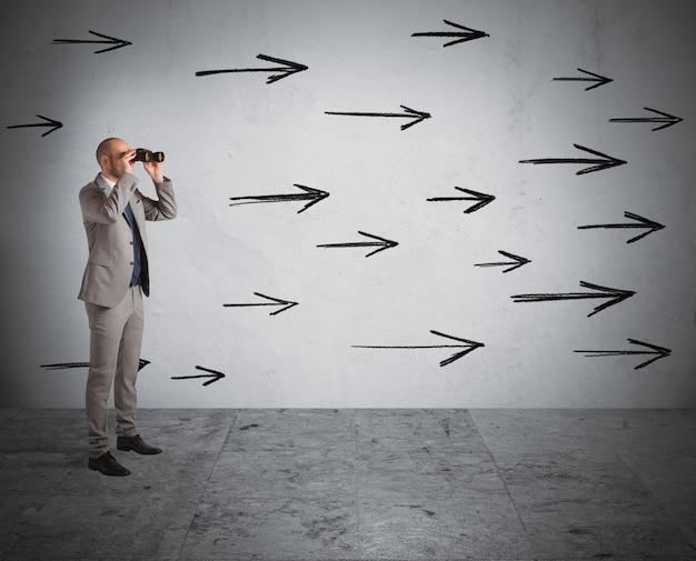 Homem olhando através de binóculos com setas na parede