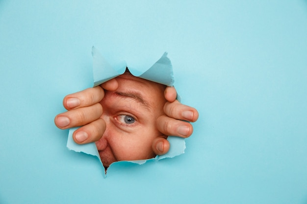 Homem olhando através do fundo azul rasgado.