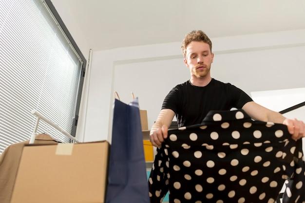Homem olhando camisa com pontos