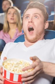 Homem olhando chocado assistindo filmes no cinema local