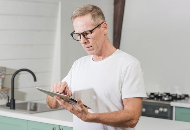 Homem olhando concentrado em seu tablet