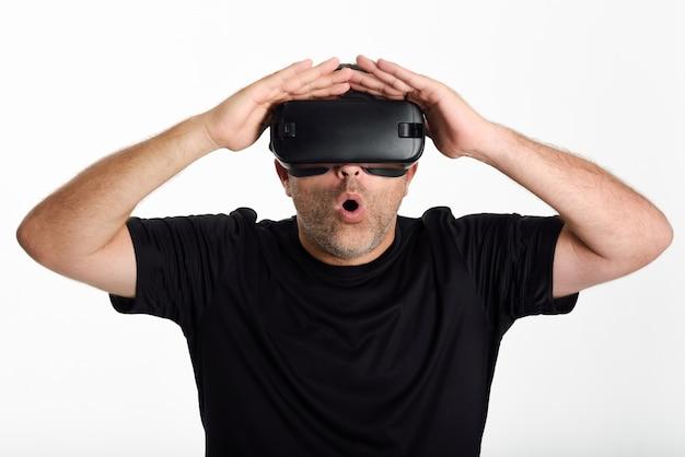 Homem olhando em óculos vr e gesticulando com as mãos.