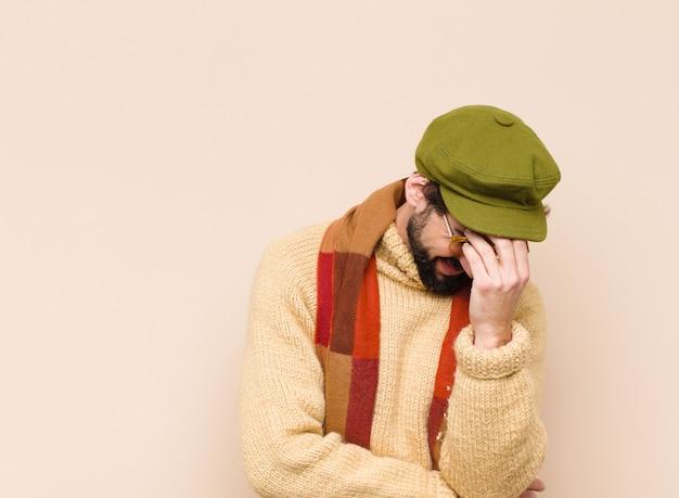 Homem olhando estressado, envergonhado ou chateado, com dor de cabeça, cobrindo o rosto com a mão