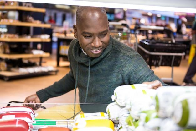Homem olhando mercadorias na seção de compras enquanto fazia compras