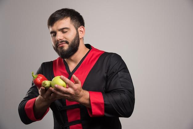 Homem olhando na pimenta vermelha, maçã e abobrinha.
