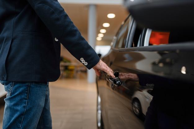 Homem olhando no interior do transporte na concessionária de automóveis. cliente em showroom de veículos novos, homem comprando automóvel, concessionária de automóveis