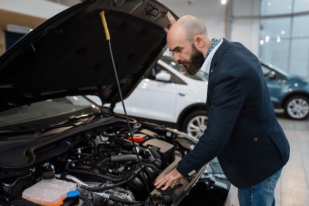 Homem olhando no motor de transporte na concessionária de automóveis. cliente em showroom de veículos novos, homem comprando automóvel, concessionária de automóveis