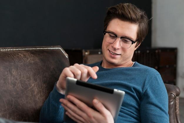 Homem olhando no seu tablet enquanto fica no sofá