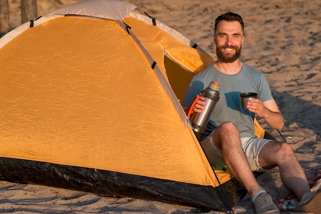 Homem olhando para a câmera segurando uma garrafa térmica