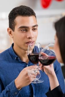 Homem olhando para a namorada, segurando um copo de vinho