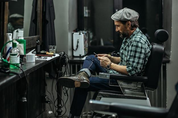 Homem olhando para a tela de seu dispositivo enquanto está sentado na barbearia