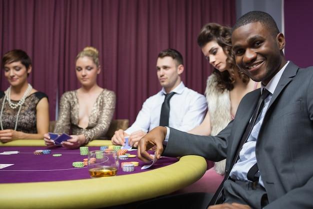 Homem olhando para cima do jogo de poker e sorrindo