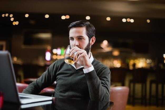 Homem olhando para laptop enquanto toma um copo de bebida