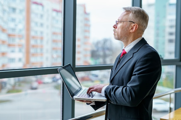 Homem olhando para longe da janela. laptop nas mãos, homem pensando enquanto verifica os e-mails em pé perto da janela. foto de lado