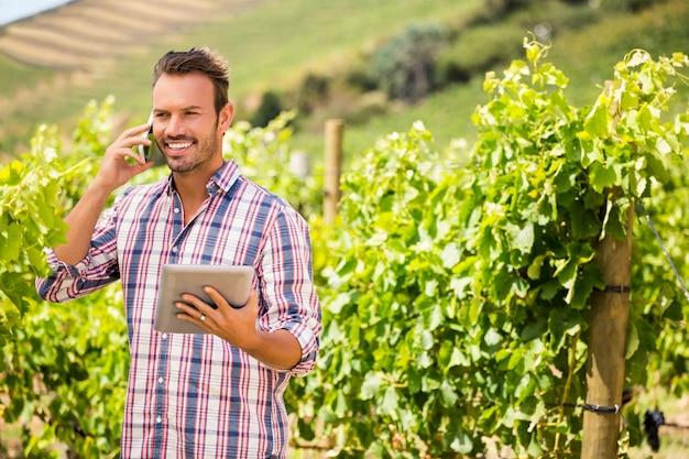 Homem olhando para longe enquanto fala ao telefone na vinha
