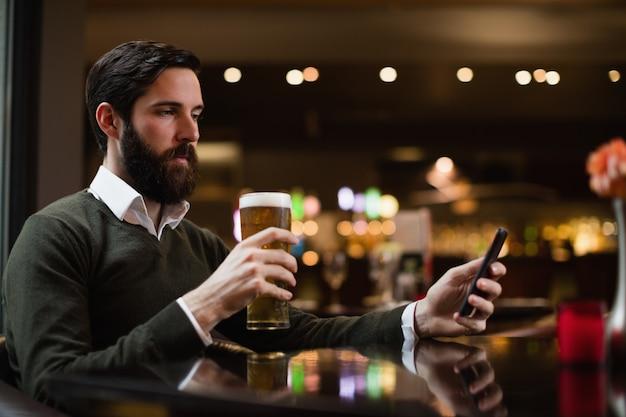 Homem olhando para o celular enquanto toma um copo de cerveja