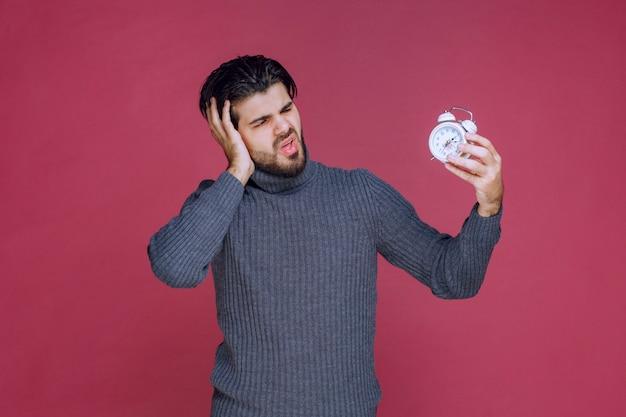 Homem olhando para o despertador e percebe que é muito cedo ou muito tarde. Foto gratuita