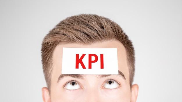 Homem olhando para o papel com a palavra kpi colada na testa