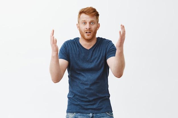 Homem olhando para o que restou de seu carro, sentindo-se chocado, parado sobre uma parede cinza em estupor. retrato de homem ruivo europeu surpreso, desapontado e chateado, gesticulando com as palmas das mãos e deixando cair o queixo