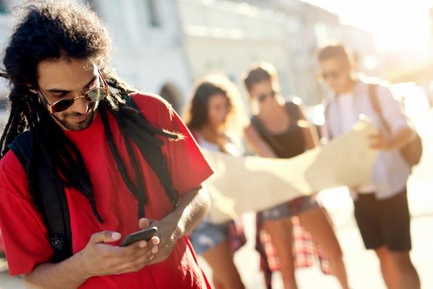 Homem olhando para o telefone móvel, pesquisando on-line para onde ir em seguida, felizes turistas descobrindo novos locais.