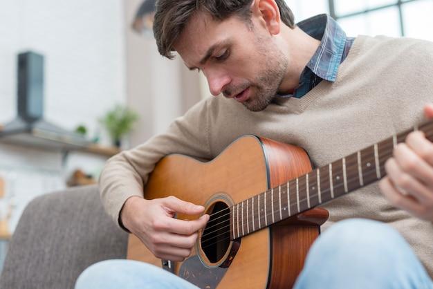 Homem olhando para o violão e toca