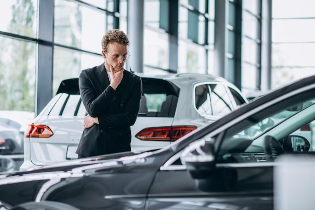 Homem olhando para um carro e pensando em uma compra