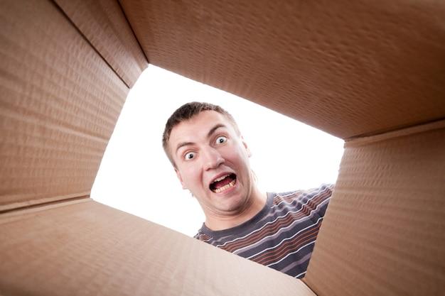 Homem olhando para uma caixa de papelão
