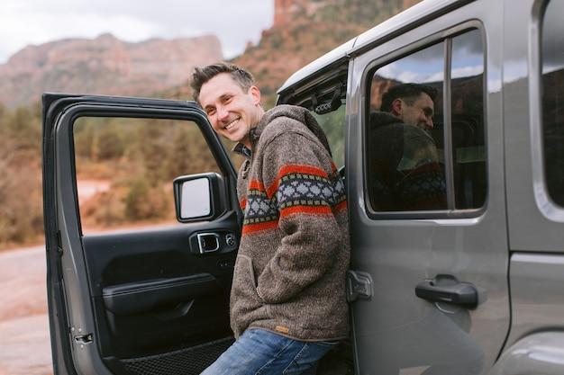 Homem olhando pela porta aberta de seu carro esporte preto
