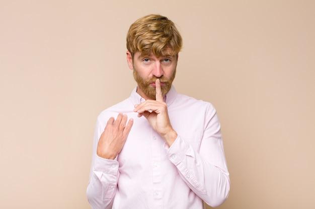 Homem olhando sério e cruzar com o dedo pressionado aos lábios exigindo silêncio ou silêncio, mantendo um segredo