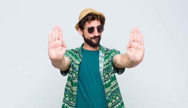 Homem olhando sério, infeliz, irritado e descontente proibindo a entrada ou dizendo pare com as duas palmas abertas