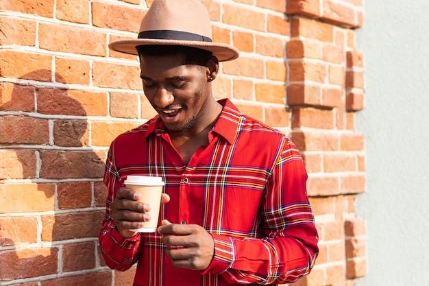 Homem olhando seu café na rua