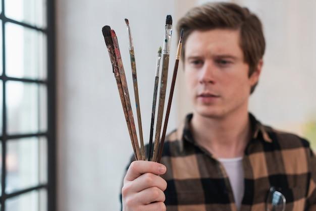 Homem olhando seus pincéis de pintura