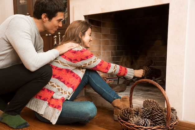 Homem, olhar, mulher jovem, colocar, pinecone, em, a, lareira