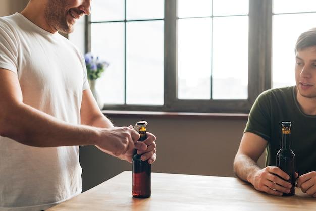 Homem, olhar, seu, amigo, abertura, a, garrafa cerveja, com, abridor, tabela