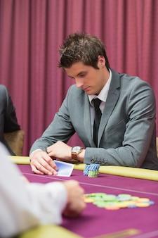 Homem, olhar, seu, cartões, em, pôquer, jogo