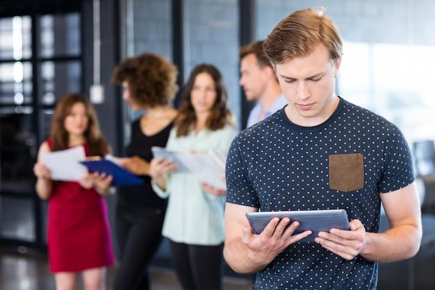 Homem, olhar, tablete digital, enquanto, dela, colegas, estar, atrás, em, escritório