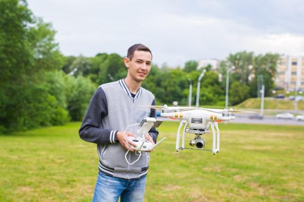 Homem operando drone voando ou pairando por controle remoto na natureza