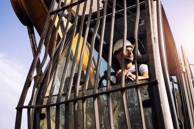 Homem operando máquina de elevação de guindaste industrial no canteiro de obras.