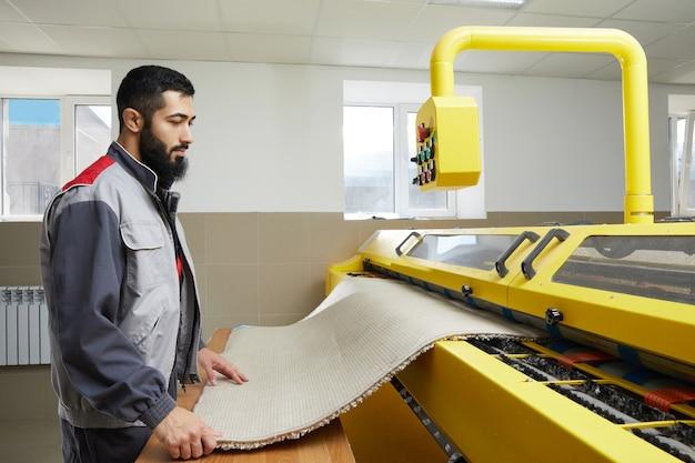 Homem operando máquina de lavar automática de carpete em serviço profissional de lavanderia