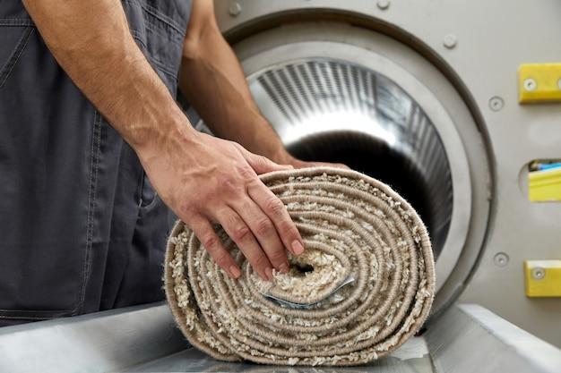 Homem operando máquina de secagem para limpeza de carpetes. serviço profissional de limpeza de carpetes