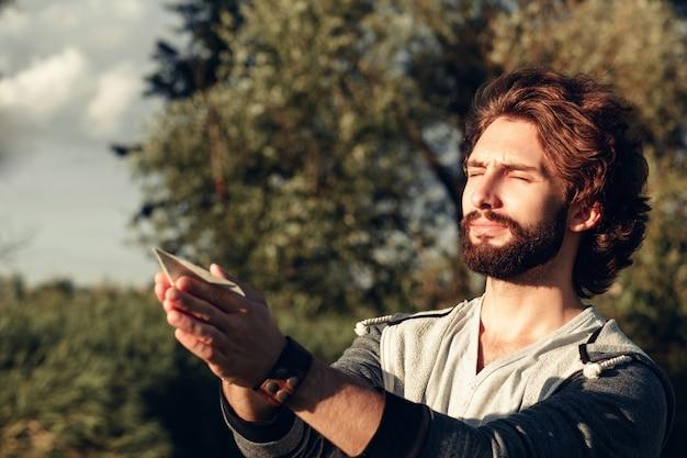 Homem orando com avião de papel no espaço livre de mãos.